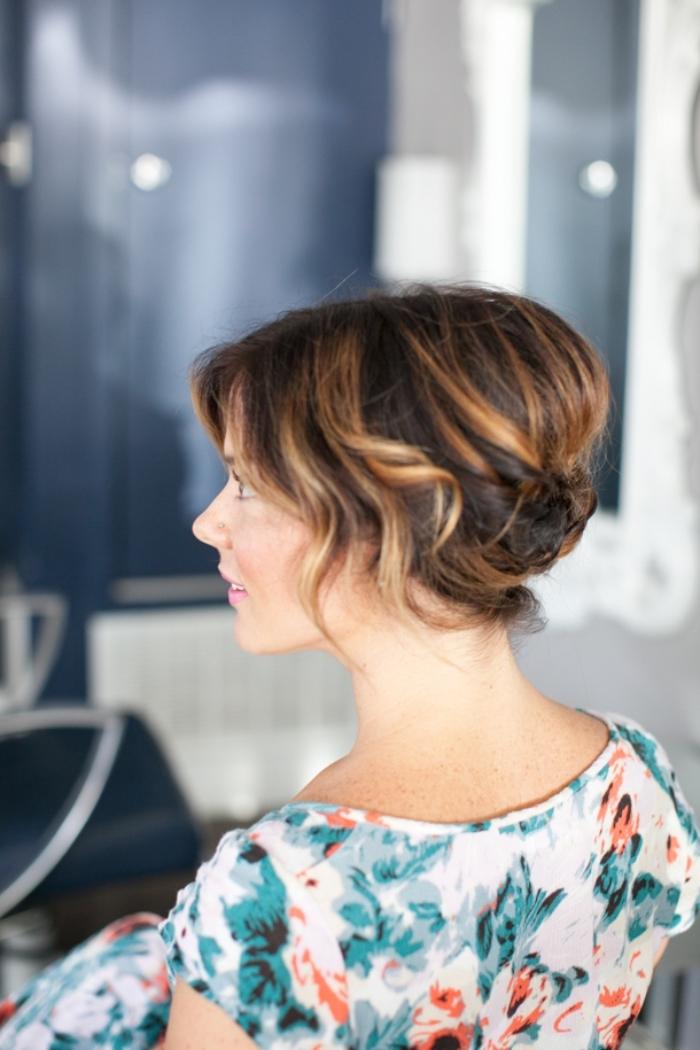 coupe de cheveux femme, coiffure en chignon banane réalisé avec boucles courts sur cheveux foncés avec mèches éclaircies