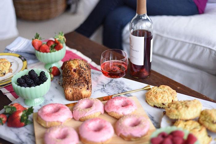 petit repas gourmand avec des beignets, pain , fruits et diverses gourmandises, bouteille de vin, idee cadeau saint valentin