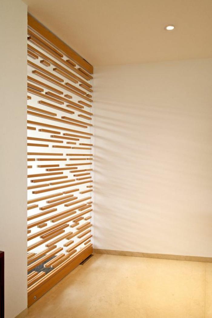 panneau en bois, avec des larges ouvertures pour la lumière, séparation chambre salon, style arty, sol recouvert de parquet clair en PVC