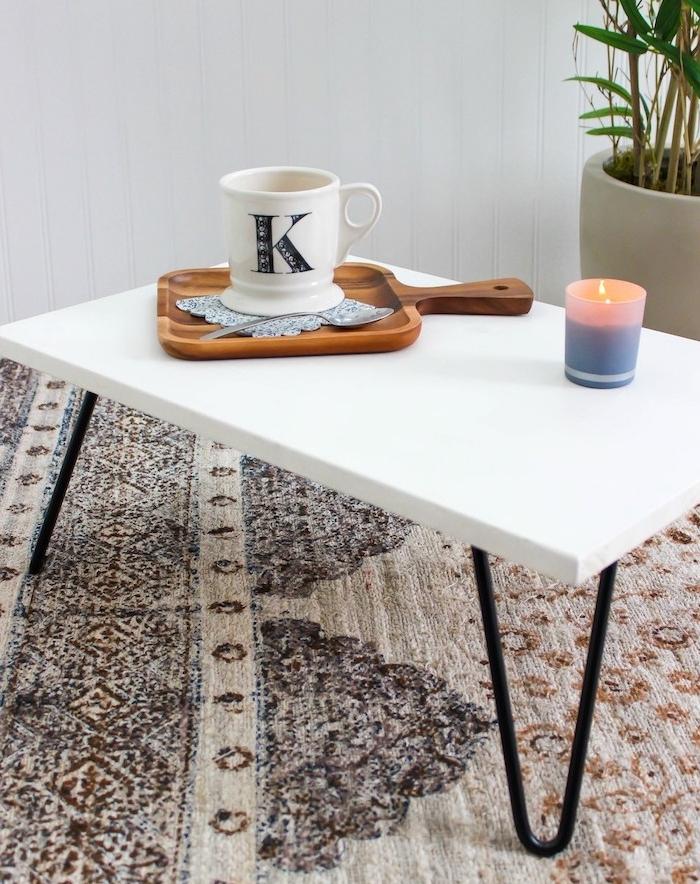 fabriquer uen table basse en plateau blanc et pieds en epingle a cheveux, tapis oriental marron et beige, bougie, plante verte