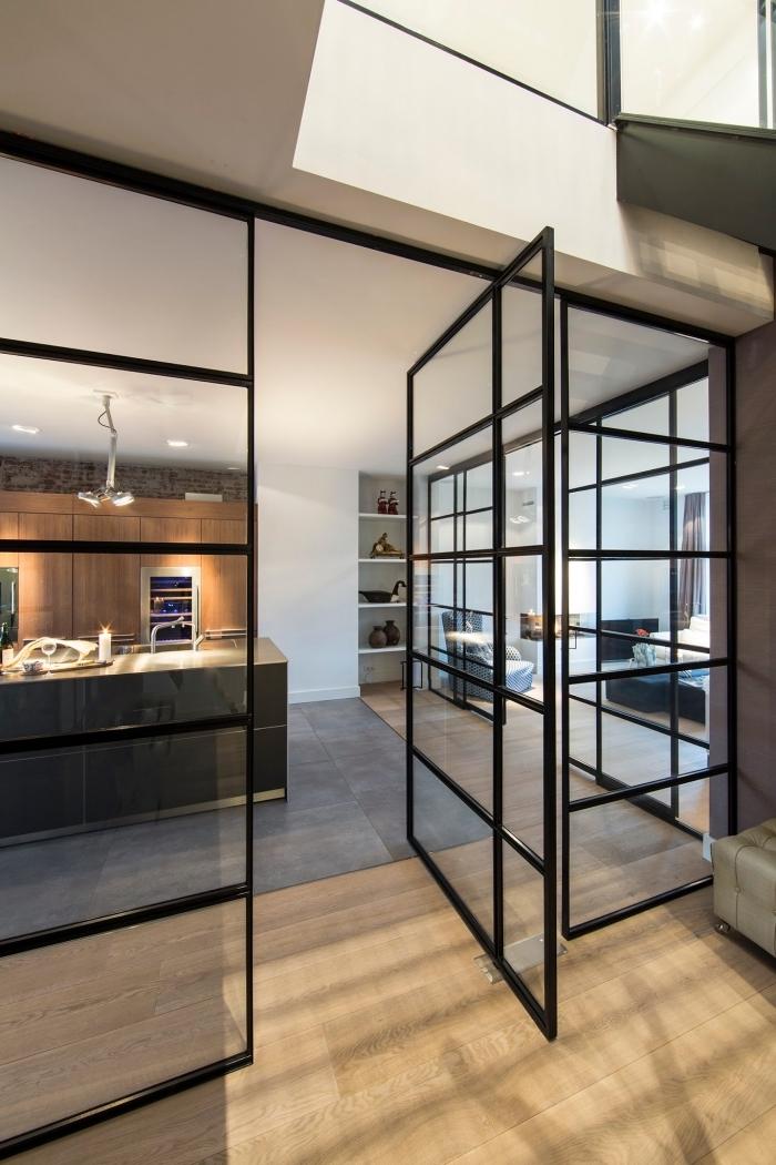 cloison atelier, grande cuisine avec parquet de bois et murs blancs équipée d'un ilot central en bois et noir