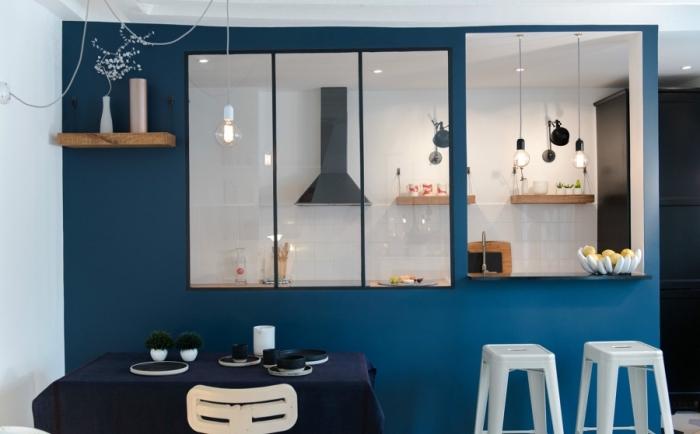 cuisine semi ouverte, pièce aux murs modernes de nuance bleu foncé avec verrières et plafond blanc