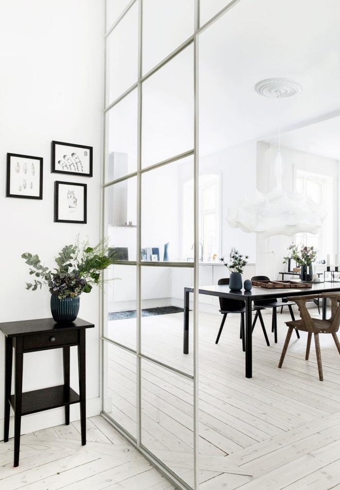 cuisine avec verrière, intérieur aux murs blancs et parquet bois avec meubles foncés et grandes fenêtres