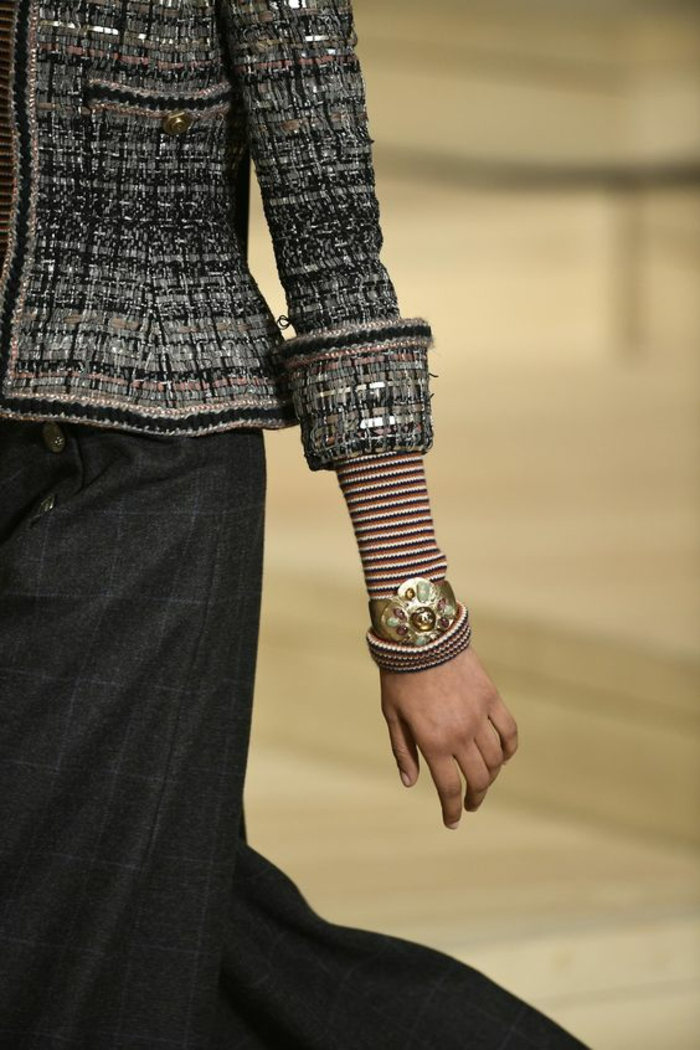 veste en gris, noir et blanc de Chanel, avec jupe grise, manches pliées laissant entrevoir des manches aux rayures rouges et blanches, haut chic bas choc