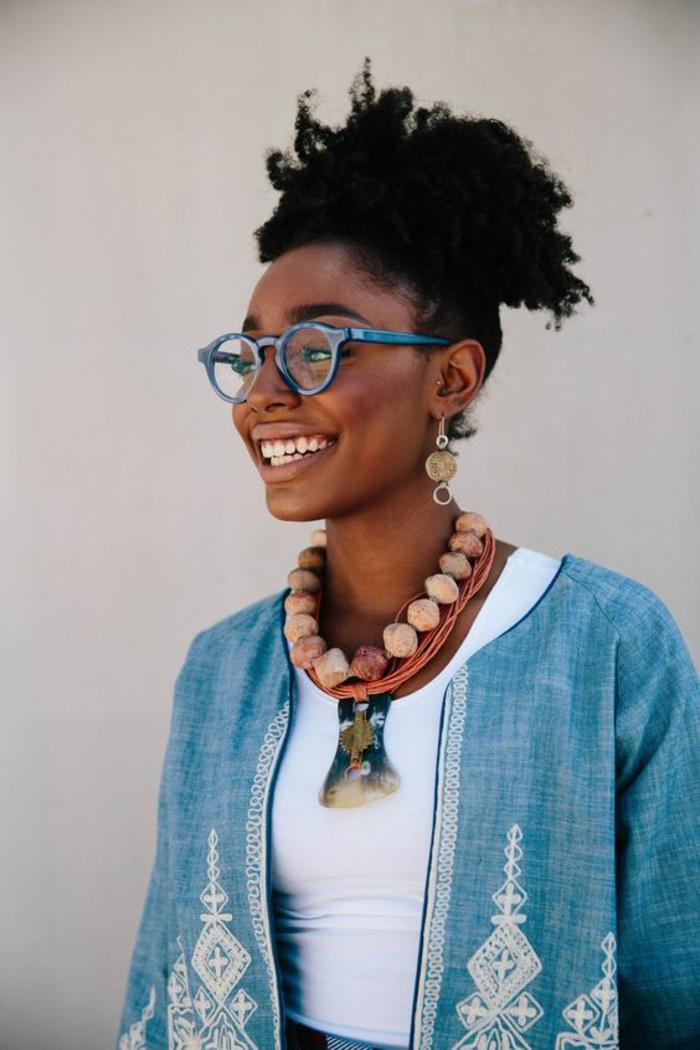 veste femme en bleu, avec des décorations arabesques et motifs ethniques en blanc, motif africain, mode africaine, collier en rose poudré avec des grandes balles, grandes montures de lunettes hipster en bleu