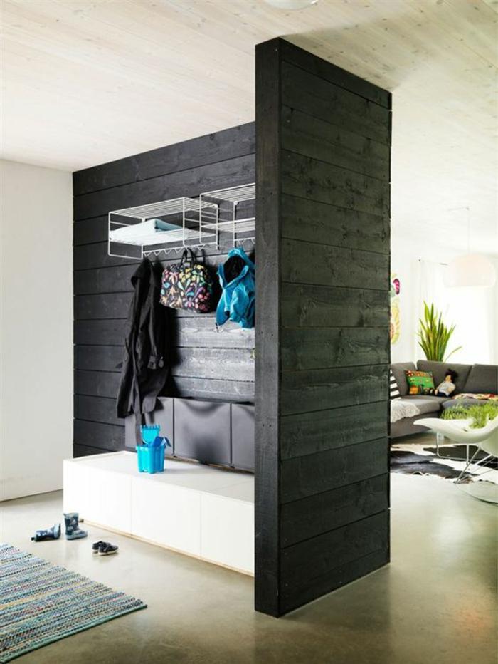 panneau de séparation en gris anthracite, en bois PVC, sol recouvert de dalles beiges, tapis carré en bleu pastel