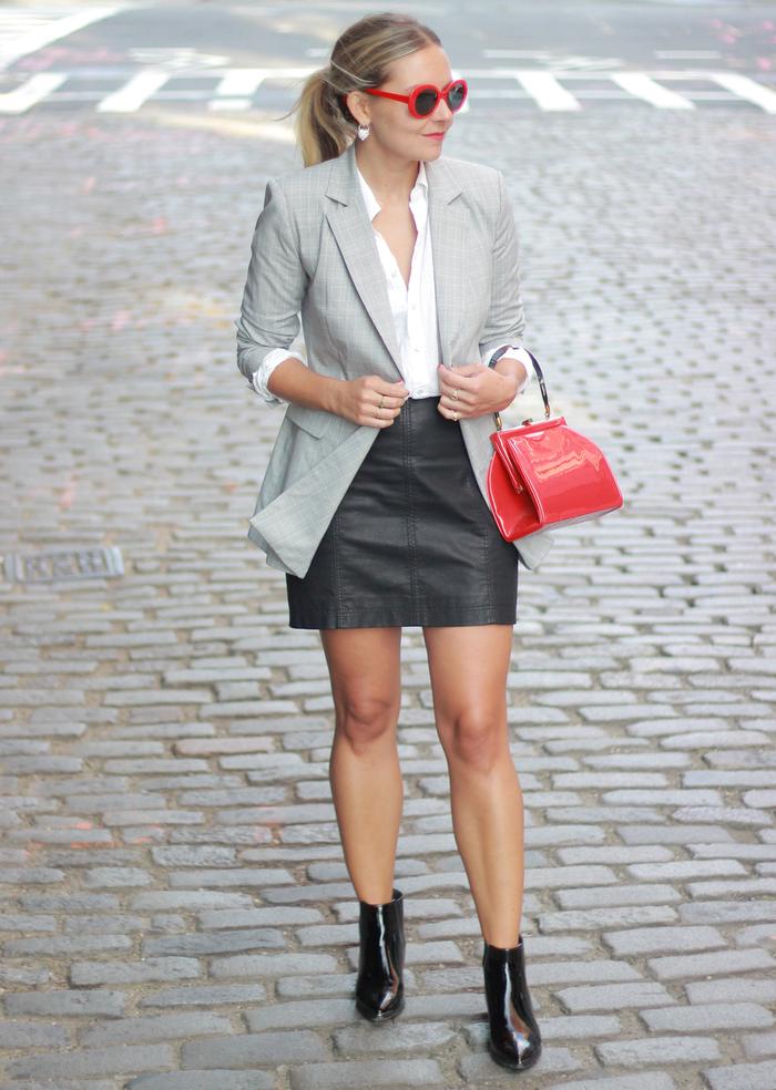 un look chic et professionnel en tailleur jupe femme dépareillé, blazer long ajusté aux manches retroussées combinée avec une jupe courte en cuir