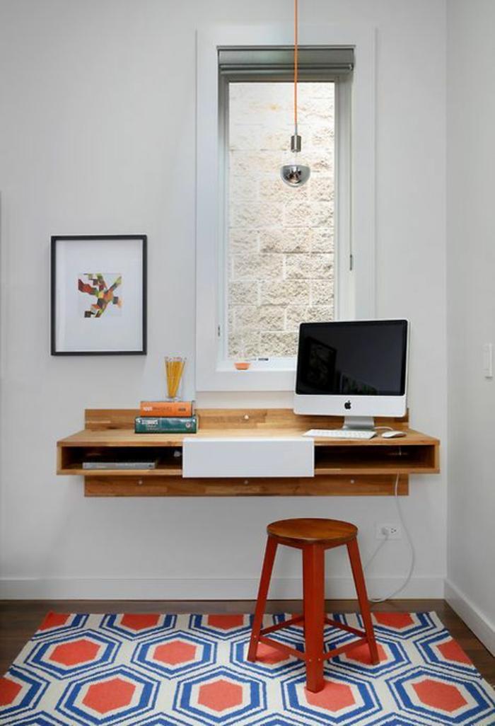 déco chambre étudiant, tapis aux motifs ruches en orange, blanc et bleu, bureau suspendu en bois clair, ordinateur grand écran, fenêtre de forme rectangulaire, tabouret en bois peint en rouge, tableau en couleurs vives au cadre noir fin