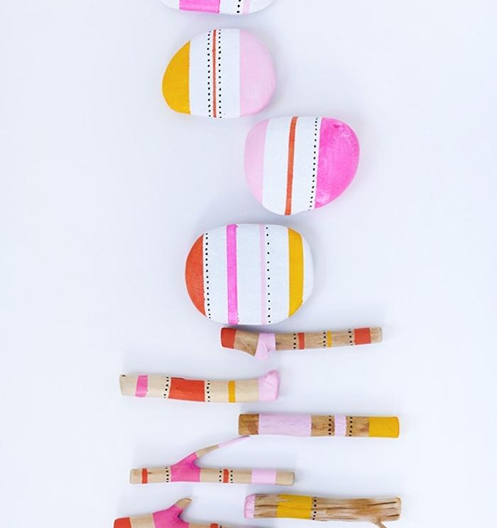exemple de brindilles de bois et des galets décorés à motifs tribal, bandes colorées de peinture, activité créative pour accueillir le printemps