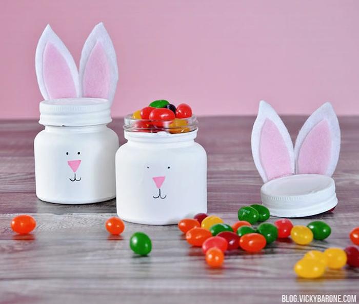 exemple d activité de paques originale avec pot en verre repeint en blanc, motif lapin de paques, dessin figure et oreilles en feutrine, boite à bonbons originale