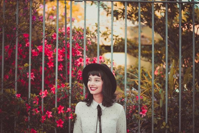 coupe de cheveux originale pour une ado, carré long sur cheveux chatain foncé avec frange sur le front, chapeau melon noir et chemise blanche avec lacets