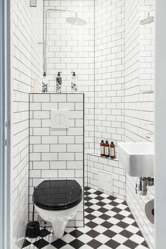aménager une petite salle de bain, carrelage mural faïence blanche, carrelage sol en motifs d'échiquier, noir et blanc, meuble wc en noir et blanc, lavabo carré en blanc, niches de rangement pour la cosmétique et les shampoings