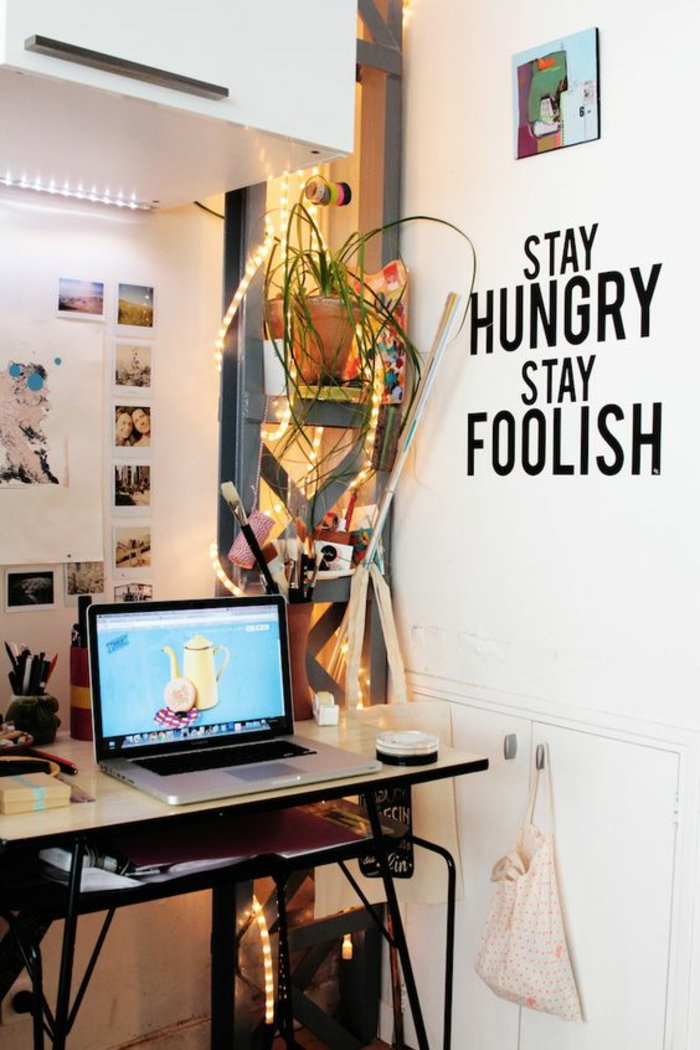 bureau aux pieds en métal noir, aménagement chambre 10m2, mur blanc avec inscription en noir, guirlande lumineuse enroulée autour du porte-plante dans le coin études