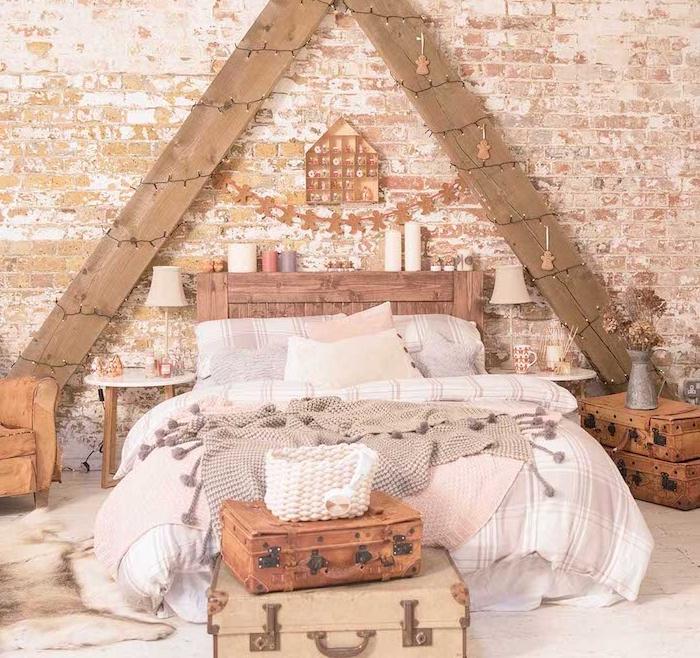 deco chambre vintage cocooning, triangle de planches de bois décorées de guirlande de noel, tete de lit originale en bois avec bougies, linge de lit gris et blanc, bout de lit en malles vintage