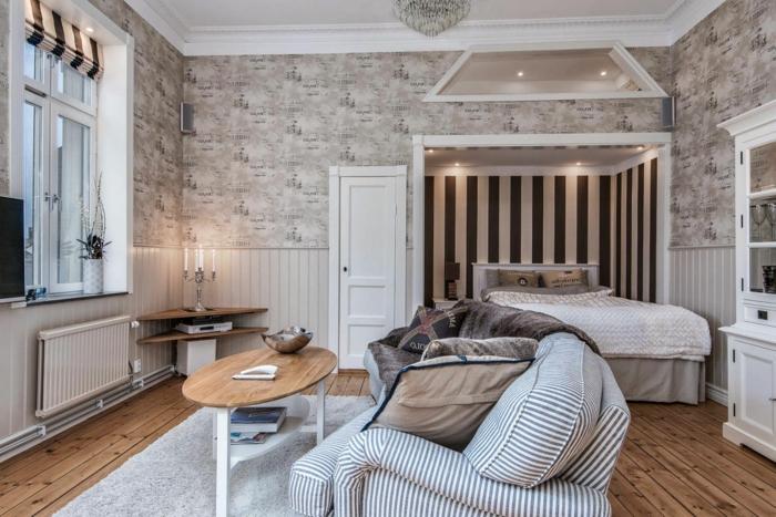alcôve pour le lit, petite table en bois ovale, sofa à rayures, tapis gris, sol en bois, plafond blanc