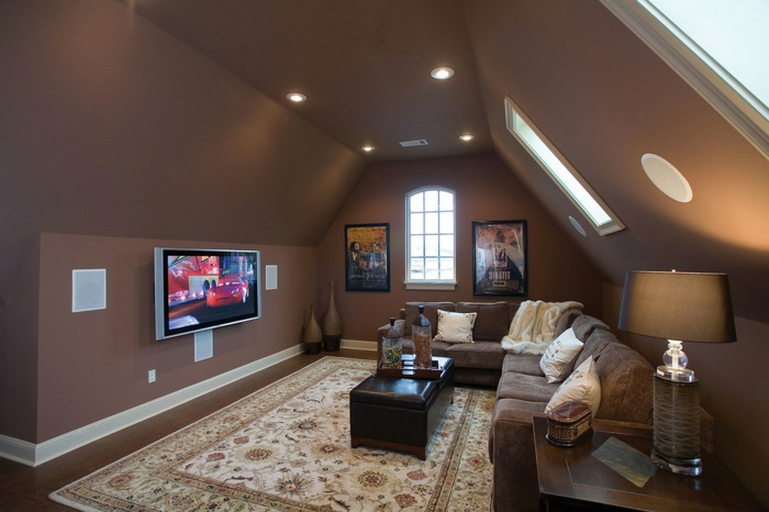 aménager des combles, tapis beige, table noire, canapé d'angle beige, peinture murale marron