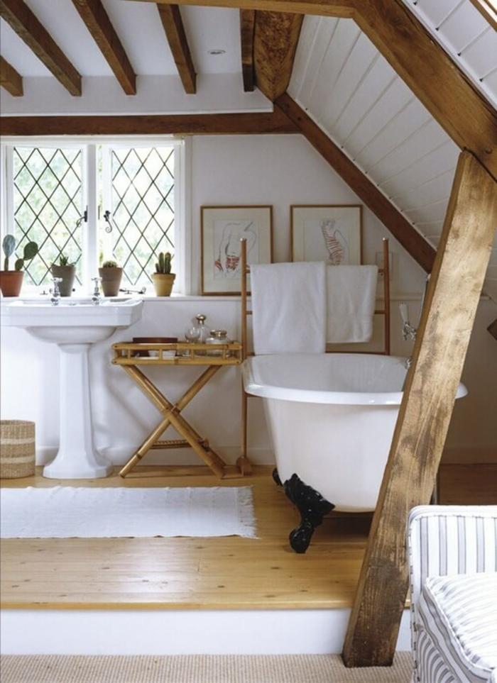 poutres apparentes dans une salle d'eau attique, amenagement salle de bain attique, baignoire vintage, sol en bois