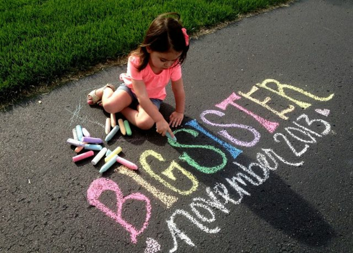 petite fille qui écrit sur l'asphalte, annoncer grossesse en écrivant avec des craies