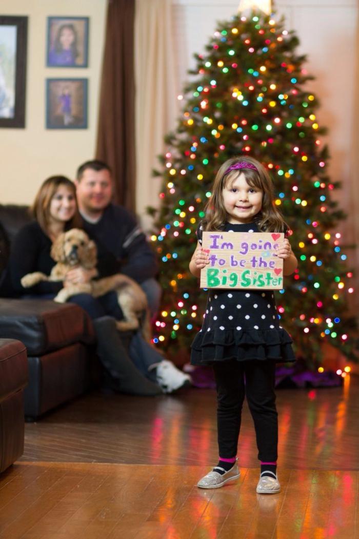une famille près du sapin de Noel, la soeur future avec un tableau avec script
