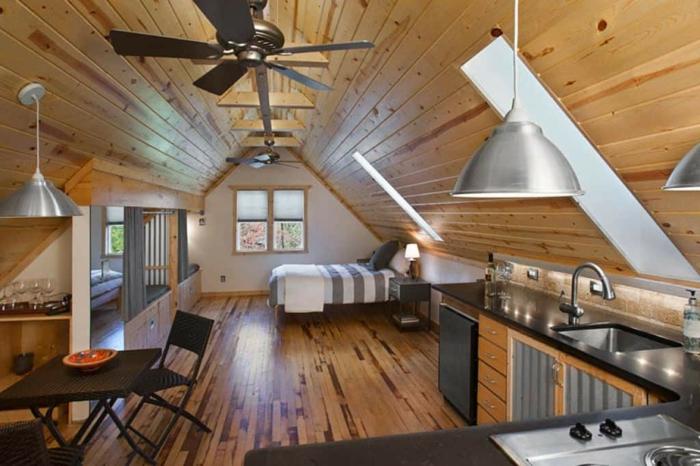petite cuisine en l, sol en bois, fenêtre en pente, lampe ventillateur, table noire avec chaises pliantes