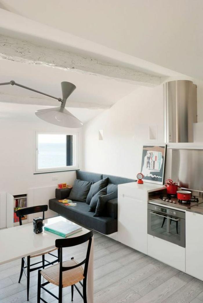 parquet blanc, luminaire blanc en métal, chambre 9m2, canapé gris anthracite, avec quatre grands coussins carrés, table rectangulaire de cuisine blanche, kitchenette
