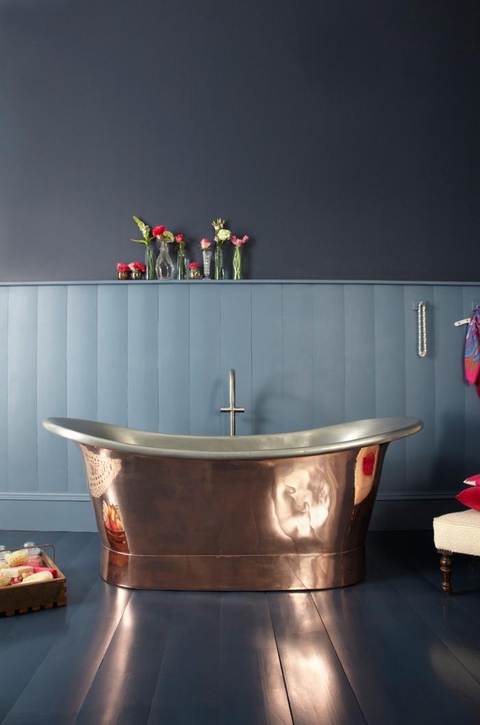 peinture murale de nuance bleu foncé avec revêtement partiel en bois peint en bleu clair, décoration avec meubles et accessoires cuivrés