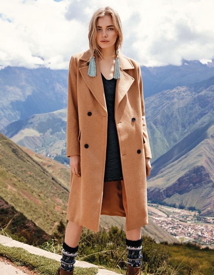 look en style bohème chic avec robe noire et bottes à design motifs ethniques, modèle de manteau loose de couleur camel avec boutons noirs