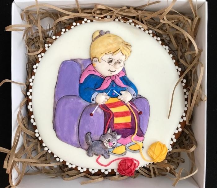 présent délicieux avec un gâteau personnalisé à design mamie aux cheveux blonds assise sur un fauteuil violet avec chien et boules de laines