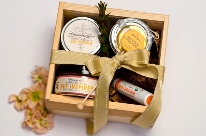 collection de produits naturels bio dans une boîte de bois avec un emballage en ruban doré, bocaux de miel bio naturel
