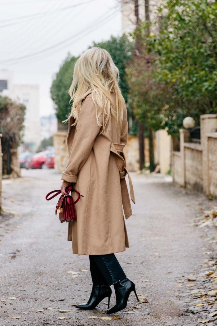 look femme stylée en manteau long camel et bottines en cuir noir à talons hautes, modèle de sac à main couleur bordeaux