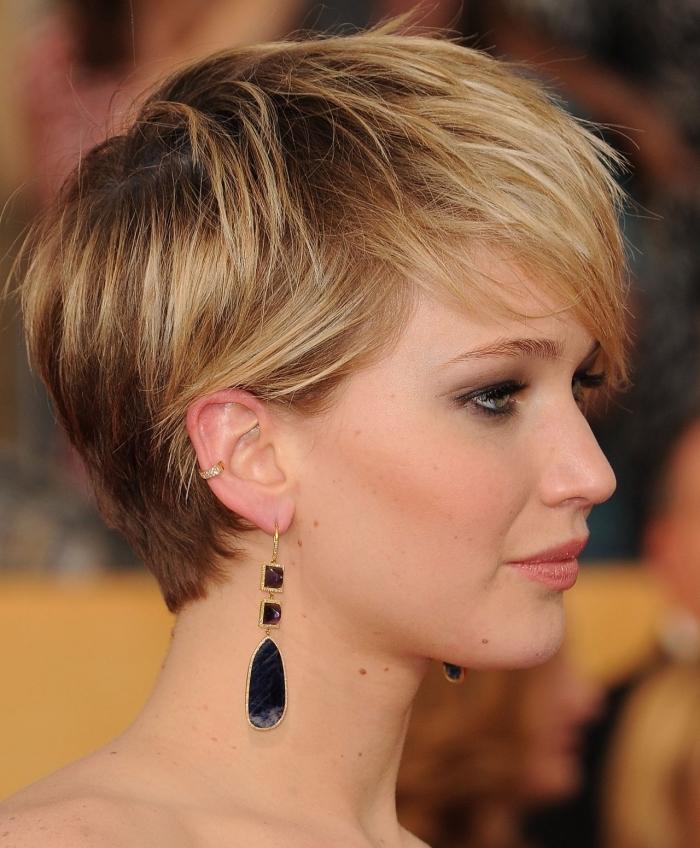Jennifer Lawrence aux cheveux courts de couleur châtain foncé avec mèches, maquillage yeux smoky et lèvres orange