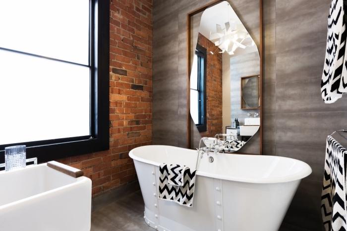 déco salle de bain dans l'esprit loft industriel avec revêtement mural en briques rouges et grande fenêtre à cadre noir mate
