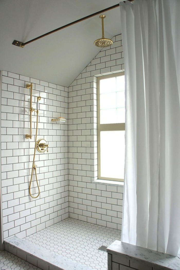 carrelage métro blanc, robinets dorés, fenêtre, cabine de douche surrélevée
