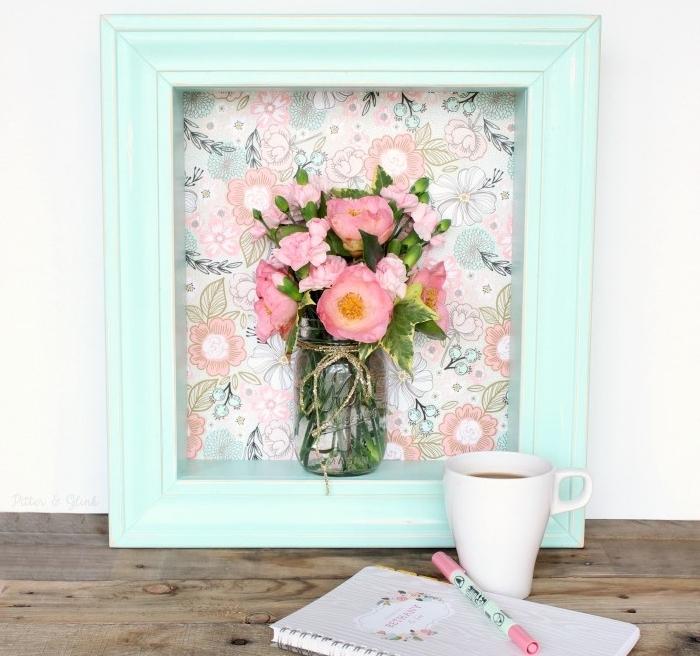 cadre repeint de peinture bleue sur un fond en tissu à imprimé floral et un pot en verre avec un bouquet de fleurs à l intérieur, idée d activité manuelle, deco printemps originale à effet 3d