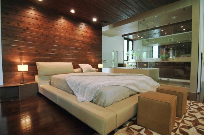 revêtement mural planches de bois, encadrement de lit en cuir beige, tapis géométrique, sol en bois