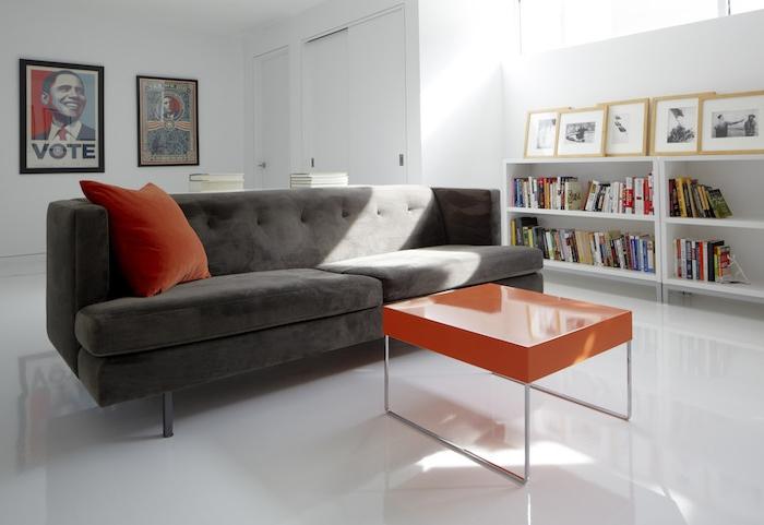 association de couleur avec le gris, canapé couleur gris anthracite, table basse et coussin décoratif orange, murs, sol et etagere blanc