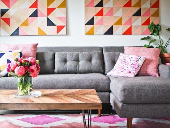 avec quelle couleur associer le gris, exemple de canapé d angle gris, coussins décoratifs rose, fleuri et à motifs géométriques, tapis rose et blanc, tableau décoratifs à figures géométriques, table en bois et métal, bouquet de fleurs