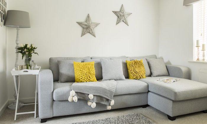 modele de canapé gris clair, coussins gris et jaune, tapis gris, mur blanc décoré d étoiles grises, table en plateau de service