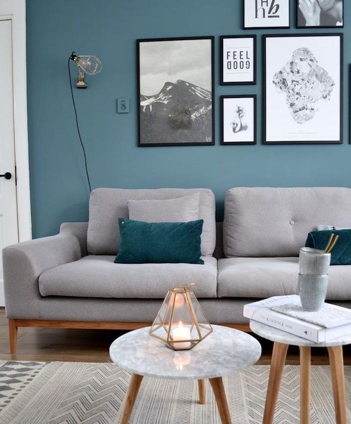 canapé gris, peinture murale bleu de gris, coussins bleu canard, table basse marbre et bois, deco murale de dessins et photos graphiques