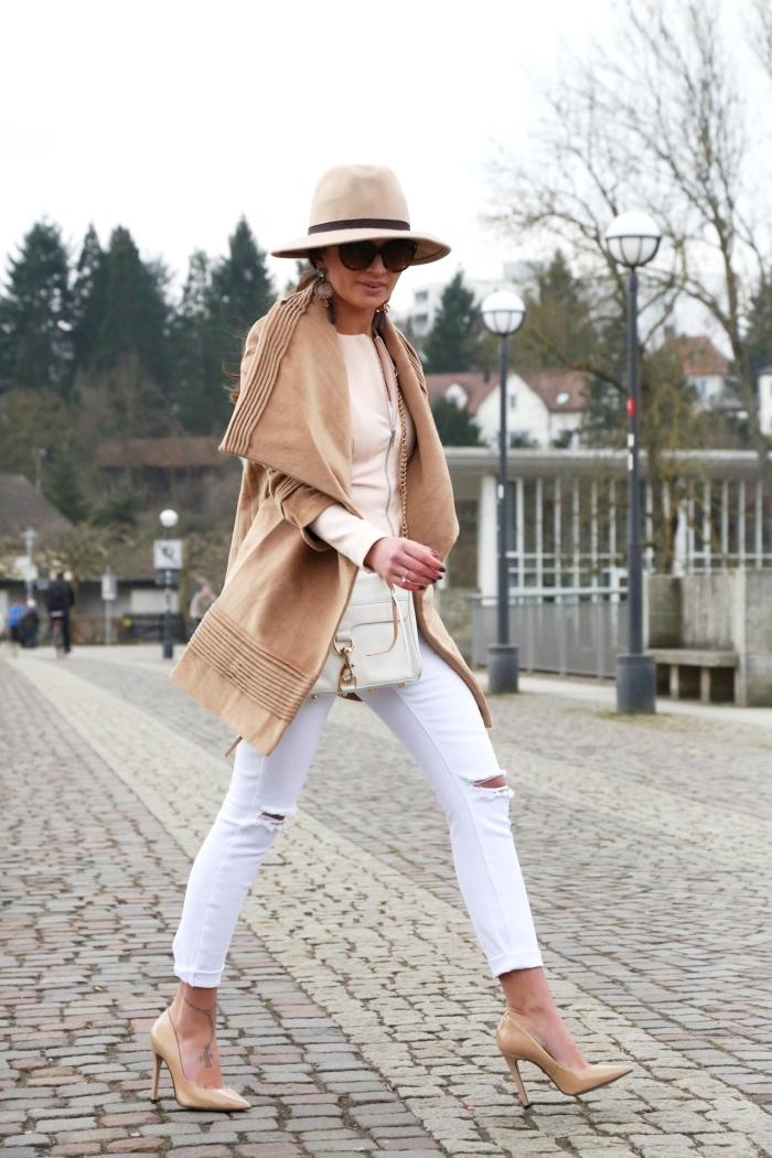 femme élégante en pantalon blanc troués sur les genoux avec manteau et chaussures camel, modèle de tatouage pied pour femme