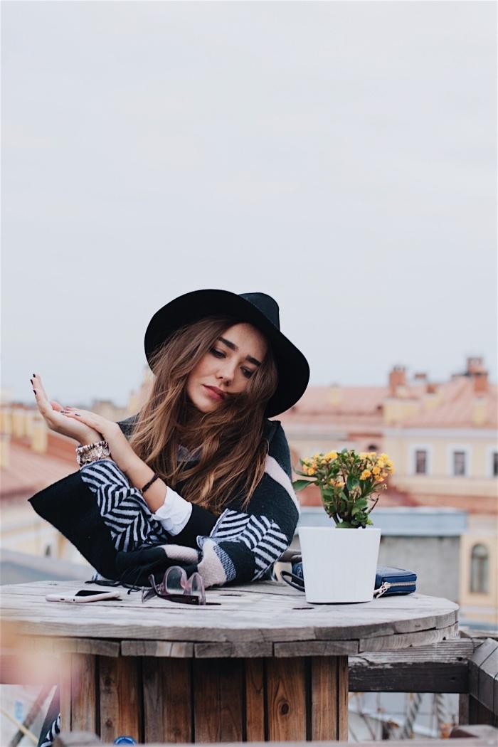 couleur chatain sur cheveux aux racines foncées et pointes éclaircies de nuance châtain clair, tenue bohème avec poncho blanc noir et capeline noire