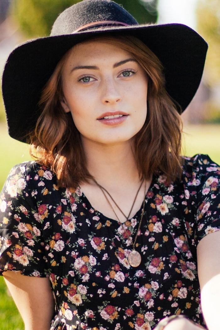 esprit bohème chic avec robe noire à motifs floraux et capeline noire, coupe de cheveux mi-longs de couleur cuivrée