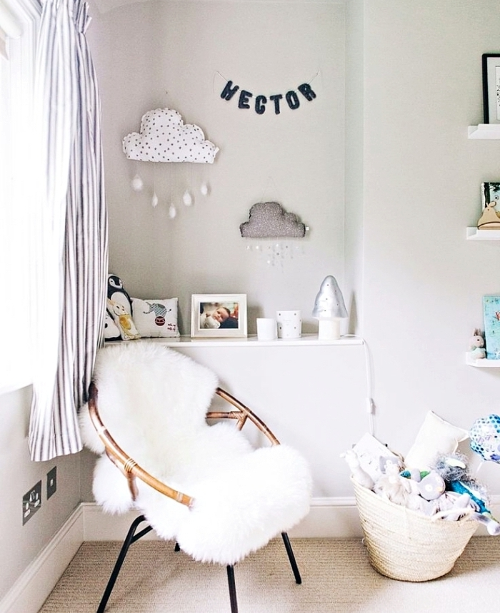 accessoires cozy dans la chambre bébé fille aux murs blancs avec objets décoratifs blancs et chaise papillon à housse blanche