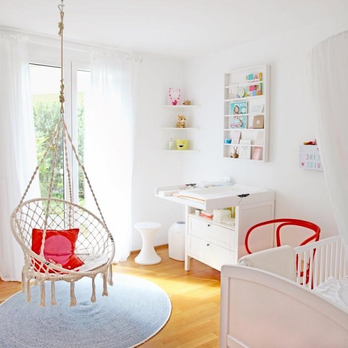 deco chambre bebe aux murs blancs et parquet de bois clair avec chaise suspendue et table à langer de bois blanc
