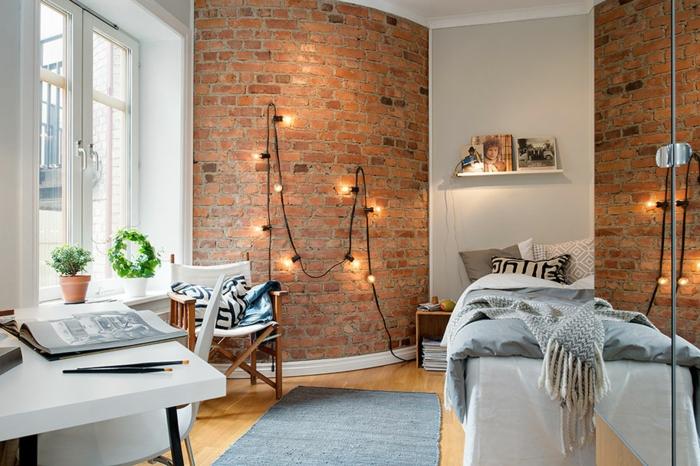 chambre scandinave en blanc et briques rouges, guirlande lumineuse, mur blanc avec petite étagère, bureau blanc