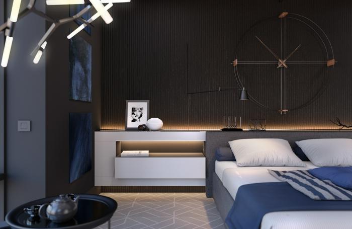 chambre en bleu et marron, horloge murale décorative, tapis beige, chevet blanc, petite table basse