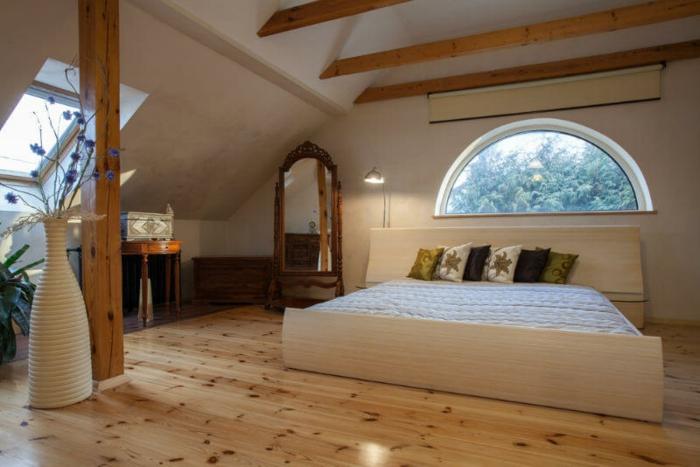 sol en bois, lit blanc, fenêtre à forme ovale, lattes de bois déco au plafond, grand vase blanc