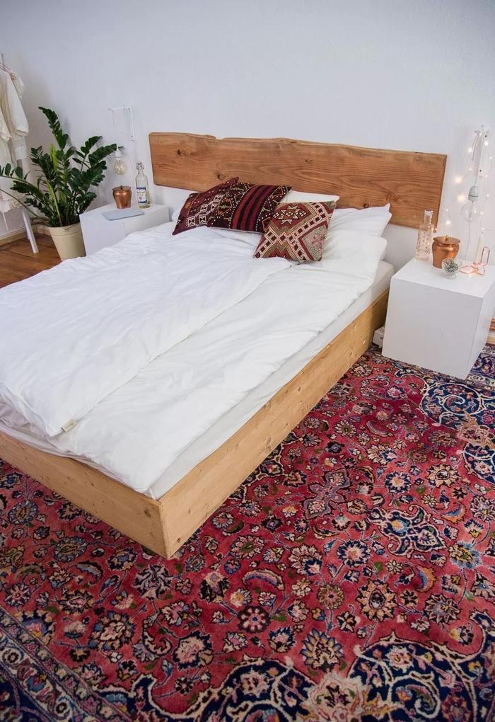 ambiance bohème chic dans la chambre à coucher avec un tapis persan, des coussins qui reprennent ses motif et une tete de lit bois brut
