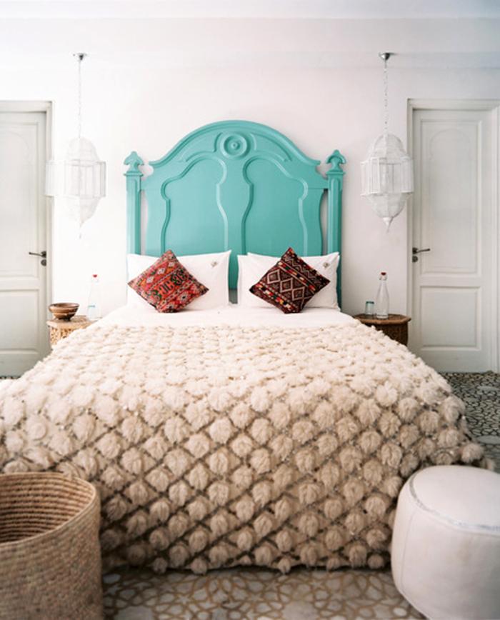 chambre à coucher d'ambiance marocaine où on mise sur les textiles typiques et la tete de lit bois turquoise
