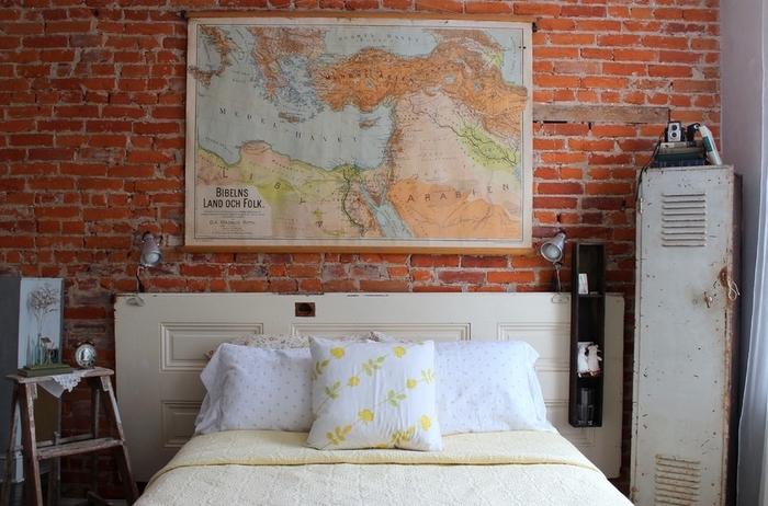une chambre à coucher esprit loft industriel avec un mobilier industriel, mur de briques exposées et une tete de lit bois récup